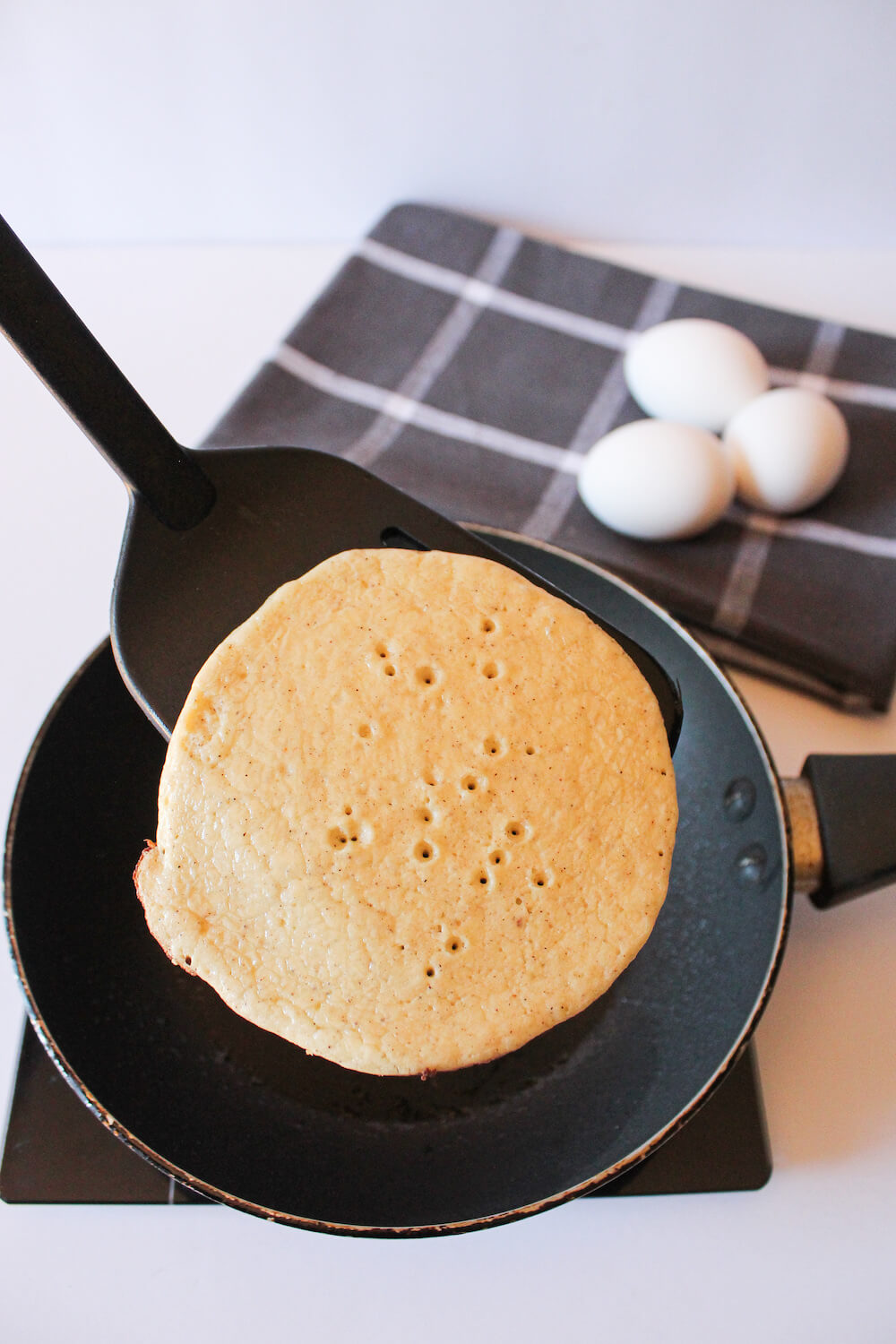 Flipping a keto almond flour pancake in the pan