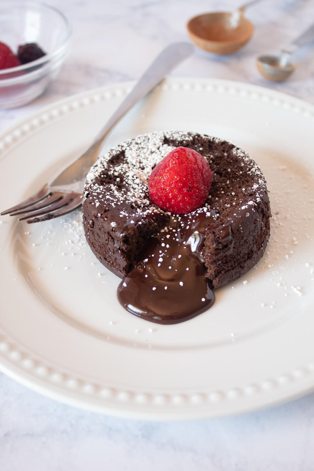 Keto Lava Cake dessert recipe served on a white plate with a fresh strawberry on top.